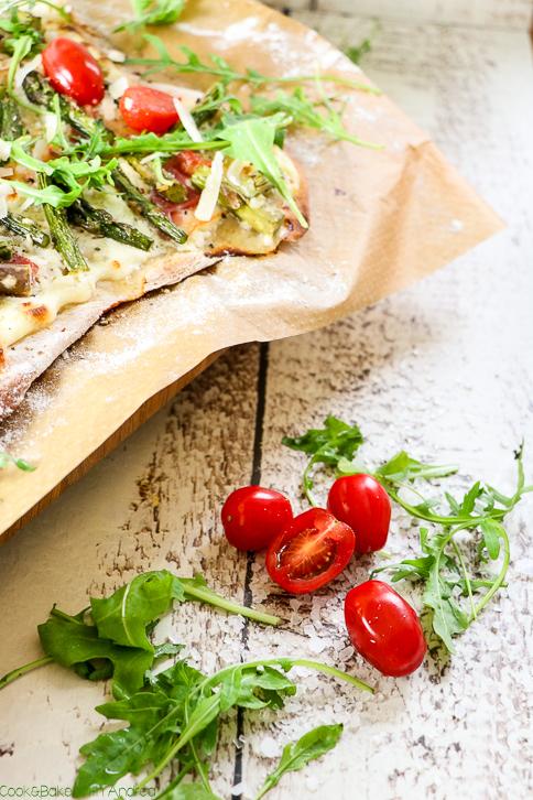 Pizza ist immer eine gute Idee, aber es muss nicht immer der Klassiker mit Tomatensoße sein. Denn mein Rezept für Pizza sieht Schmand, grünem Spargel, Speck, Rucola und feinen Cherrytomaten für den perfekten Belagn vor. Das einfache Rezept findet ihr bei Cook and Bake with Andrea.