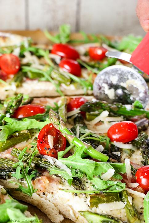 Pizza ist immer eine gute Idee, aber es muss nicht immer der Klassiker mit Tomatensoße sein. Denn meine Frühlingspizza wird mit Schmand, grünem Spargel, Speck, Rucola und feinen Cherrytomaten belegt. Das einfache Rezept findet ihr bei Cook and Bake with Andrea.